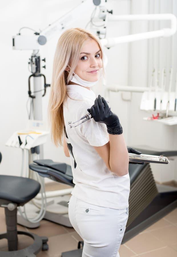 Ritratto di giovane dentista femminile attraente che tiene strumento dentario all'ufficio dentario moderno fotografia stock libera da diritti