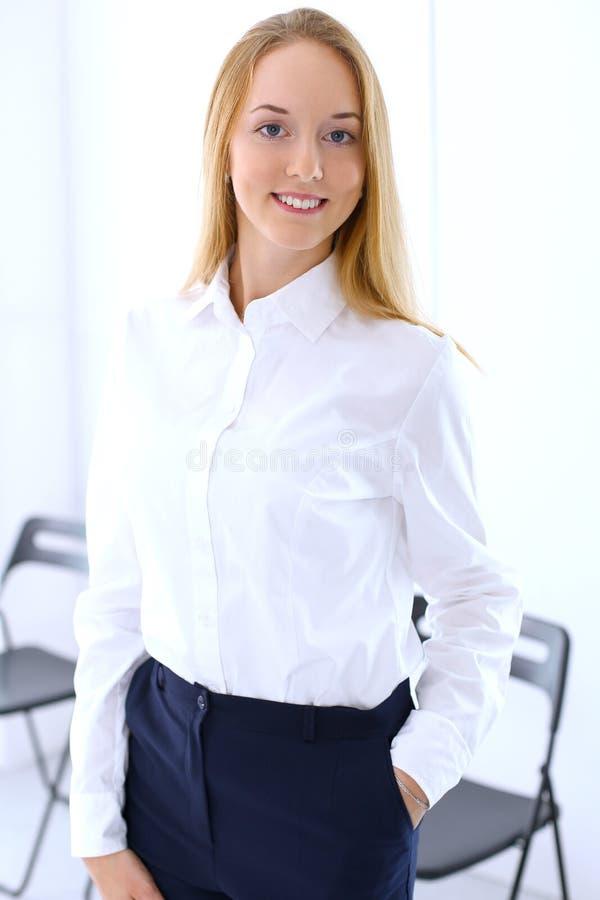 Ritratto di giovane donna di affari bionda nel fondo dell'ufficio fotografie stock