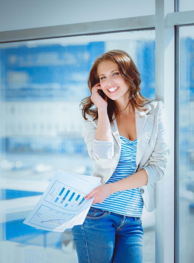 Ritratto di giovane donna di affari che parla sul telefono cellulare nel corridoio dell'ufficio immagine stock