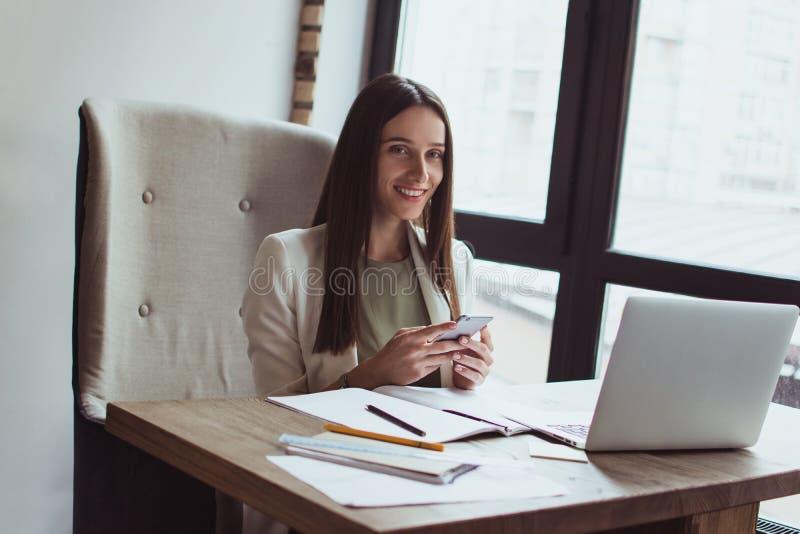 Ritratto di giovane donna di affari che si siede con il suo computer portatile nell'ufficio immagine stock libera da diritti