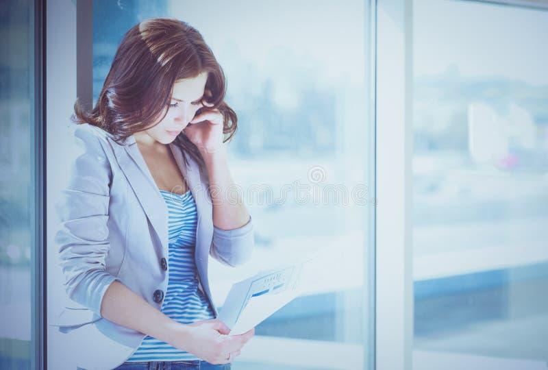 Ritratto di giovane donna di affari con il telefono cellulare sul corridoio dell'ufficio fotografie stock libere da diritti