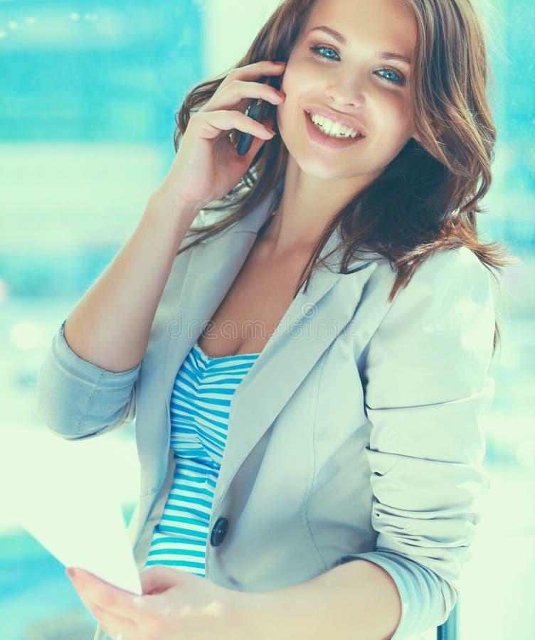 Ritratto di giovane donna di affari con il telefono cellulare sul corridoio dell'ufficio fotografia stock