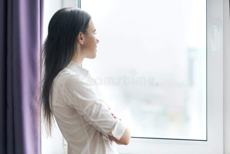 Ritratto di giovane donna di affari sicura in camicia bianca con le armi attraversate, donna che guarda fuori la finestra, uffici fotografia stock