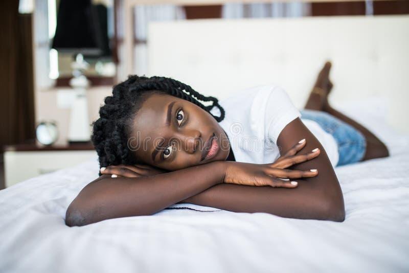 Ritratto di giovane donna africana graziosa sorridente che si rilassa a letto fotografia stock