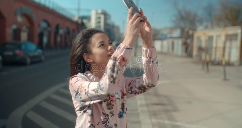 Ritratto di giovane donna afroamericana che per mezzo del telefono, all'aperto immagine stock libera da diritti