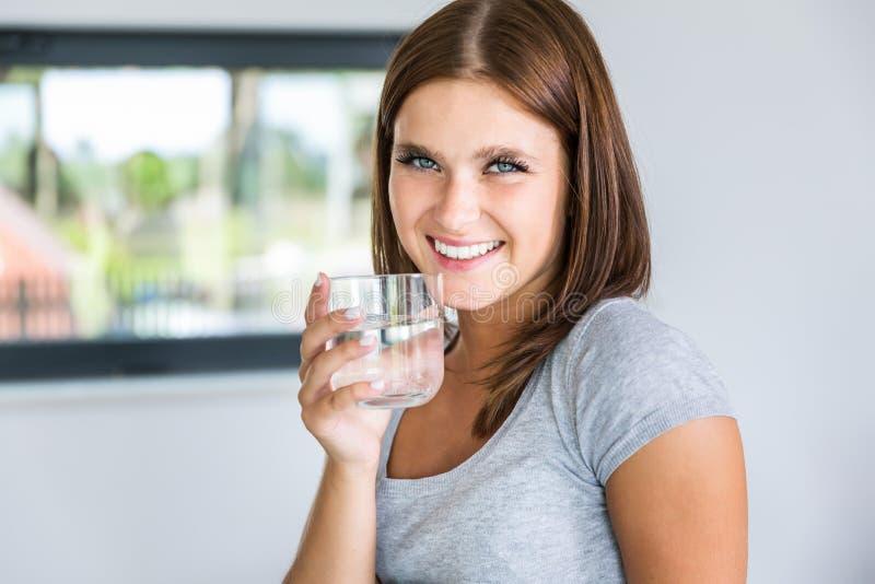 Ritratto di giovane donna allegra con vetro di acqua minerale fotografia stock