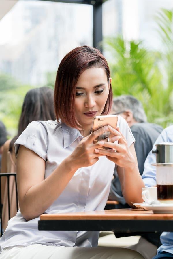 Ritratto di giovane donna asiatica che per mezzo di un telefono cellulare ad un caffè fotografie stock