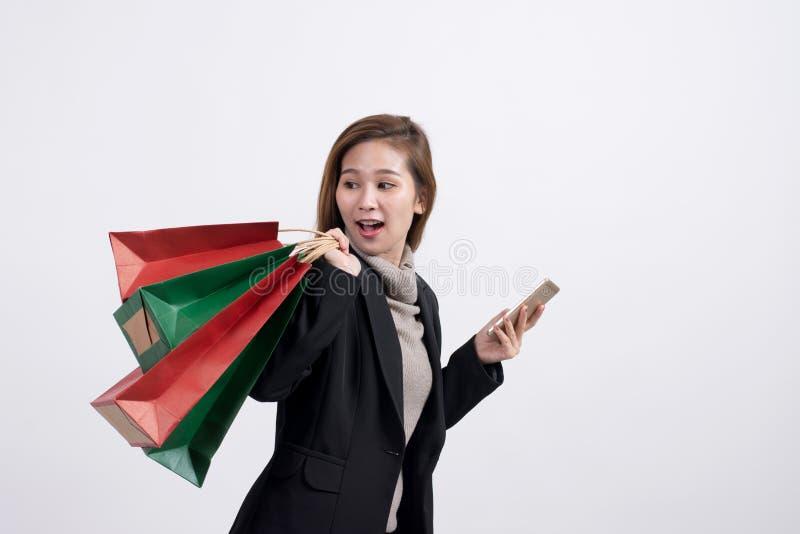 Ritratto di giovane donna asiatica sorridente felice con i sacchetti della spesa e lo Smart Phone immagine stock