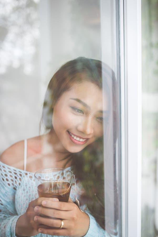 Ritratto di giovane donna asiatica splendida che si rilassa con la tazza di uff fotografie stock
