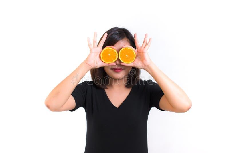 Ritratto di giovane donna asiatica tenuta le fette arancio davanti ai suoi occhi e del sorriso sopra un fondo bianco immagine stock