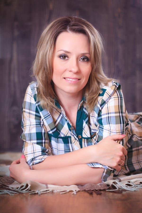 Ritratto di giovane donna attraente che si trova sulla coperta del plaid, primo piano fotografia stock libera da diritti