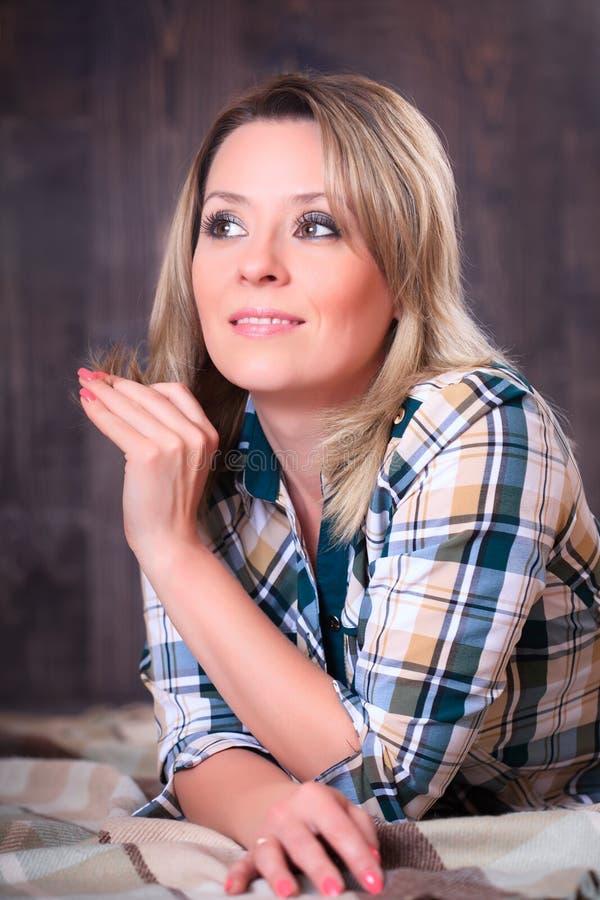 Ritratto di giovane donna attraente che si trova sulla coperta del plaid, primo piano fotografia stock