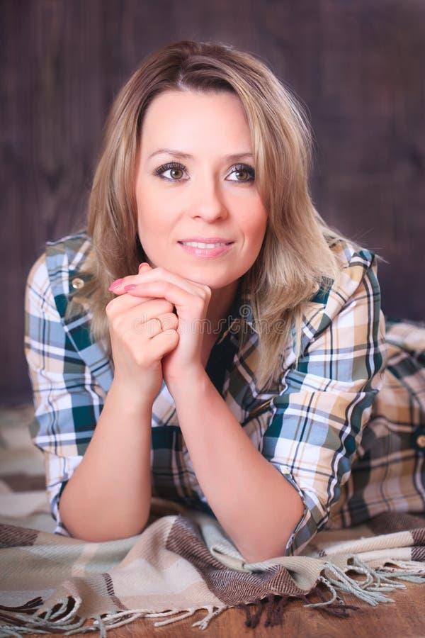 Ritratto di giovane donna attraente che si trova sulla coperta del plaid, primo piano immagini stock