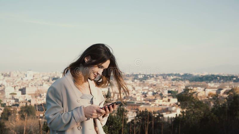 Ritratto di giovane donna attraente che sta al panorama di Roma, Italia Uso femminile lo smartphone fuori fotografie stock libere da diritti