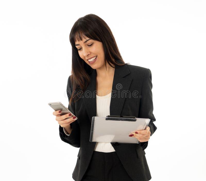 Ritratto di giovane donna attraente felice di affari che controlla i email e che manda un sms sul telefono cellulare immagini stock