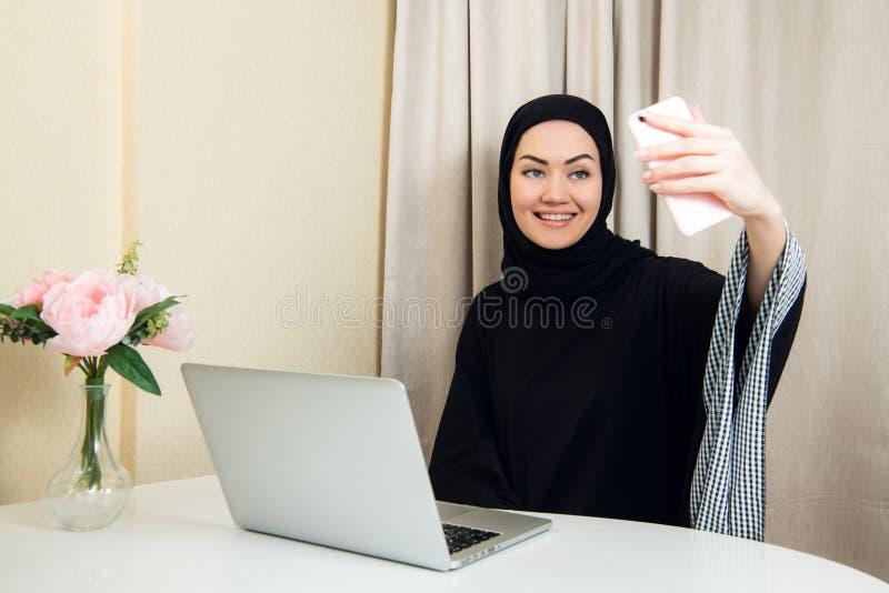 Ritratto di giovane donna attraente nel hijab che fa la foto del selfie sullo smartphone fotografia stock