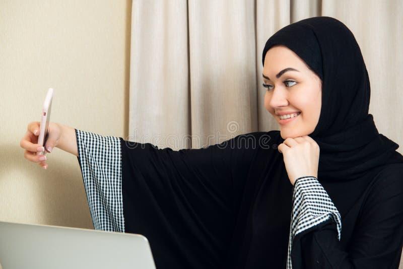 Ritratto di giovane donna attraente nel hijab che fa la foto del selfie sullo smartphone fotografie stock