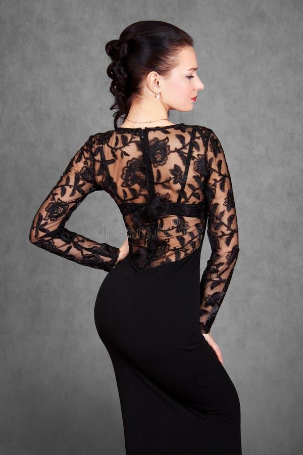 Ritratto di giovane donna attraente in un vestito da sera nero immagini stock