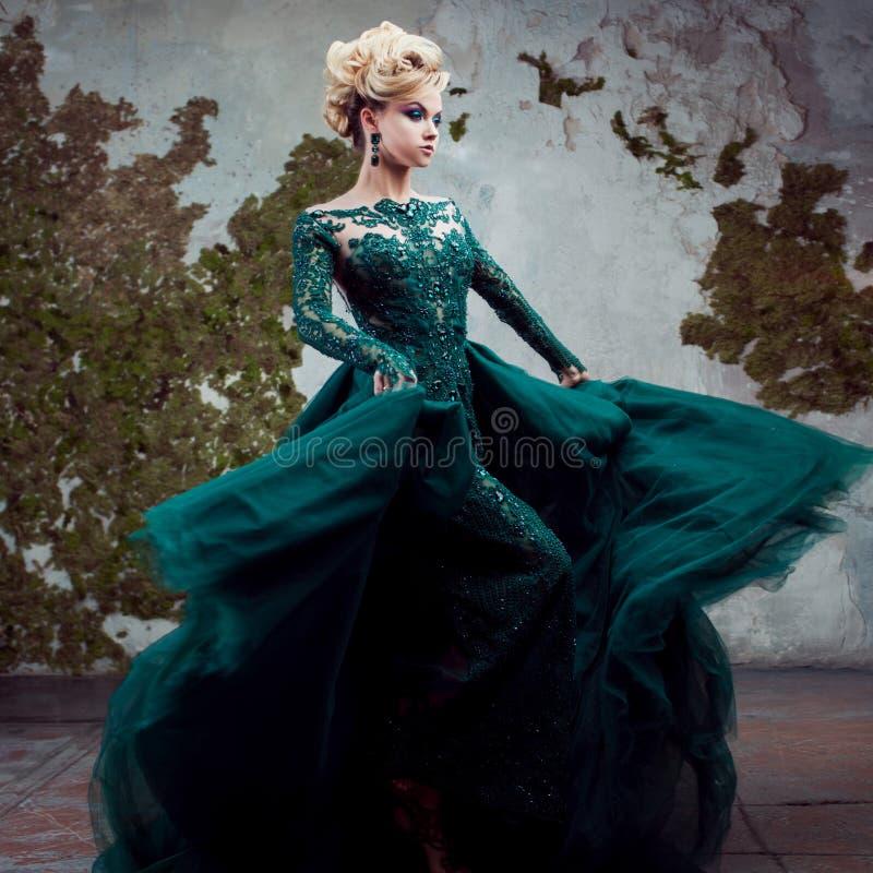 Ritratto di giovane donna bionda attraente in un bello vestito verde Fondo strutturato, interno Acconciatura di lusso fotografia stock libera da diritti