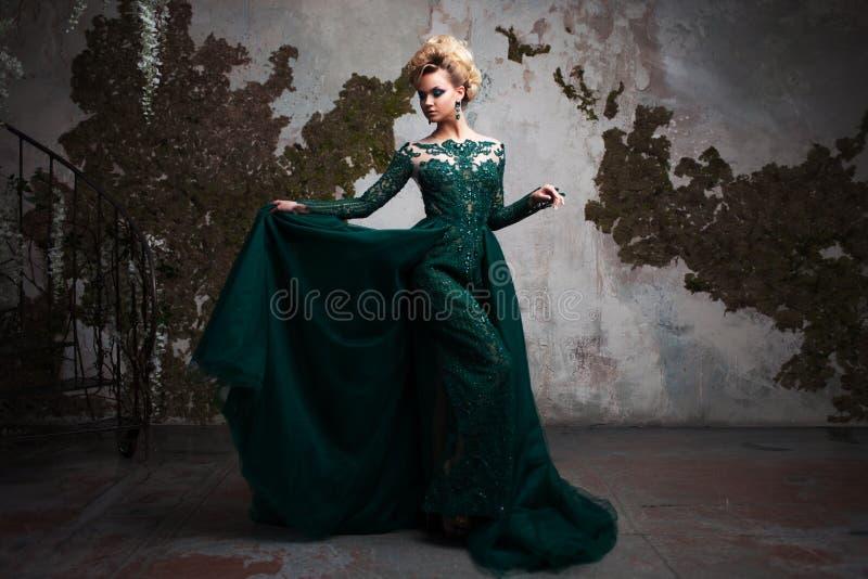 Ritratto di giovane donna bionda attraente in un bello vestito verde Fondo strutturato, interno Acconciatura di lusso immagine stock libera da diritti