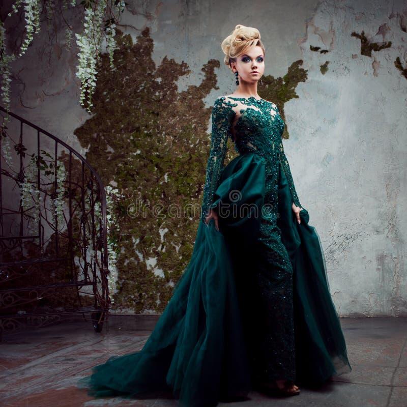 Ritratto di giovane donna bionda attraente in un bello vestito verde Fondo strutturato, interno Acconciatura di lusso fotografie stock