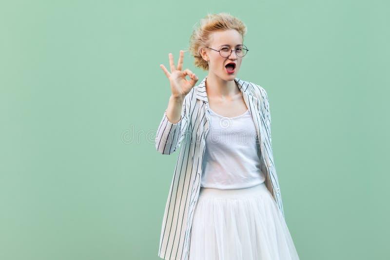 Ritratto di giovane donna bionda divertente in camicia bianca, gonna, blusa a strisce con gli occhiali che stanno con il segno di immagini stock