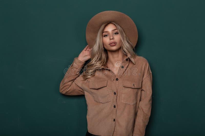 Ritratto di giovane donna bionda insolente con capelli ricci in un cappello elegante d'annata con bello trucco in una camicia d'a immagini stock libere da diritti