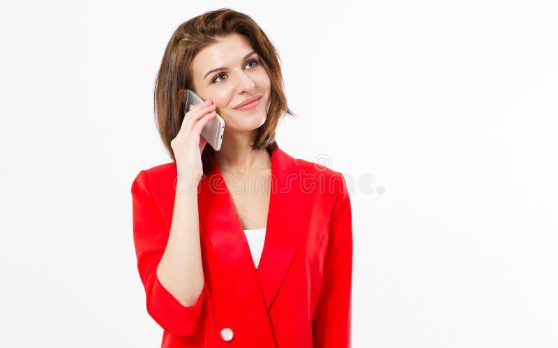 Ritratto di giovane donna castana casuale sorridente che parla sul telefono cellulare circa qualcosa isolato sopra fondo bianco - immagini stock