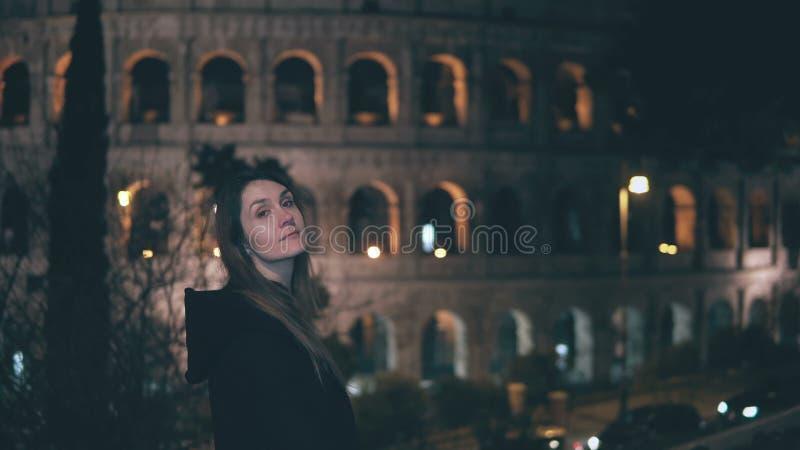 Ritratto di giovane donna castana che sta vicino a Colosseum a Roma, Italia nella sera Giri e sguardi della ragazza alla macchina fotografia stock libera da diritti