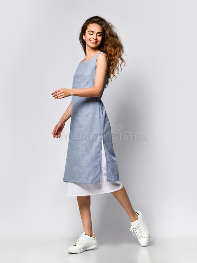 Ritratto di giovane donna castana in un vestito leggero blu che posa su un fondo leggero, modo di estate, preparante per una data fotografia stock