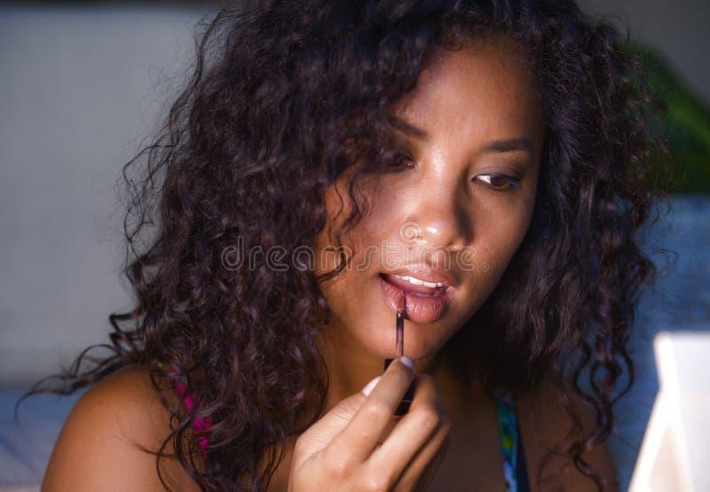 Ritratto di giovane donna caucasica e afroamericana di bella e etnia mista naturale che usando trucco sulle sue labbra a casa den fotografia stock