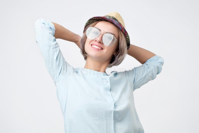 Ritratto di giovane donna caucasica graziosa in occhiali da sole e cappello fotografie stock