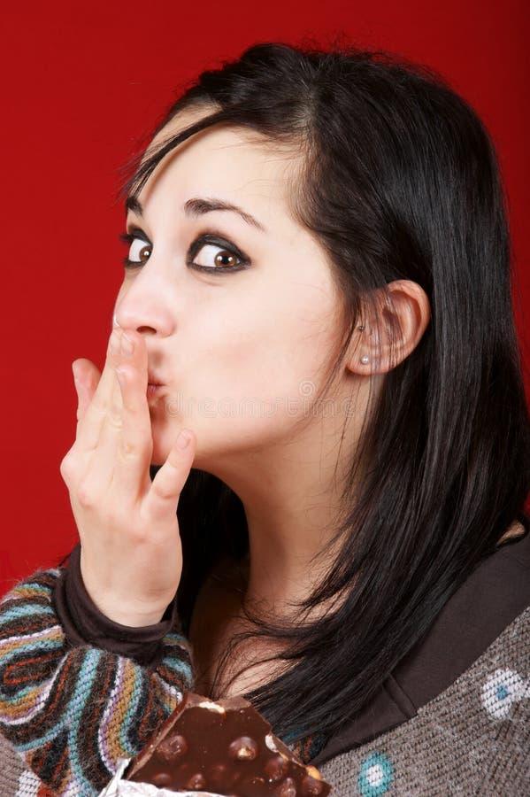 Ritratto di giovane donna che mangia cioccolato fotografie stock