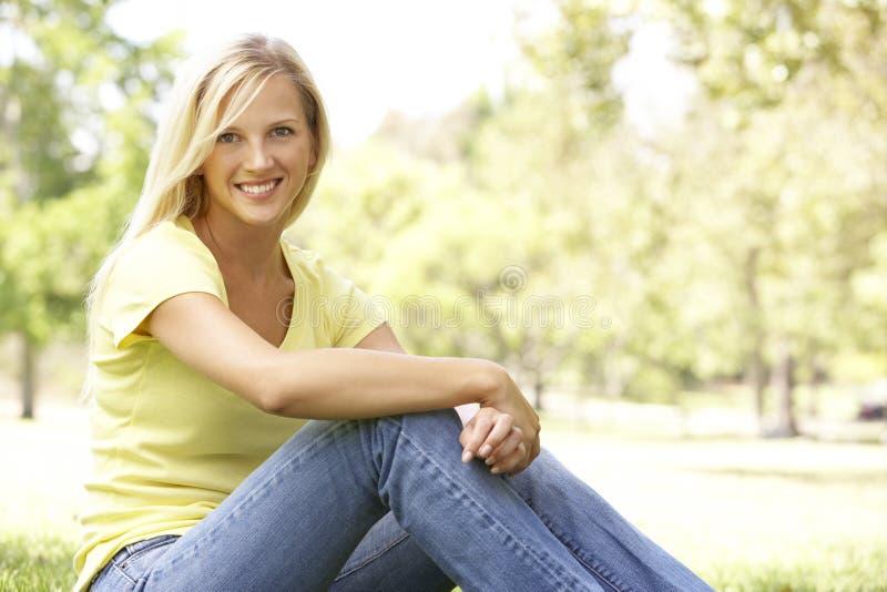 Ritratto di giovane donna che si siede nella sosta immagini stock