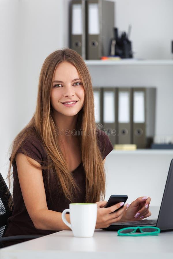 Ritratto di giovane donna di affari che lavora al suo ufficio fotografia stock libera da diritti