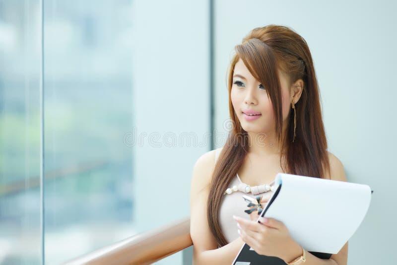 Ritratto di giovane donna di affari che sta finestra vicina in moderno fotografie stock libere da diritti