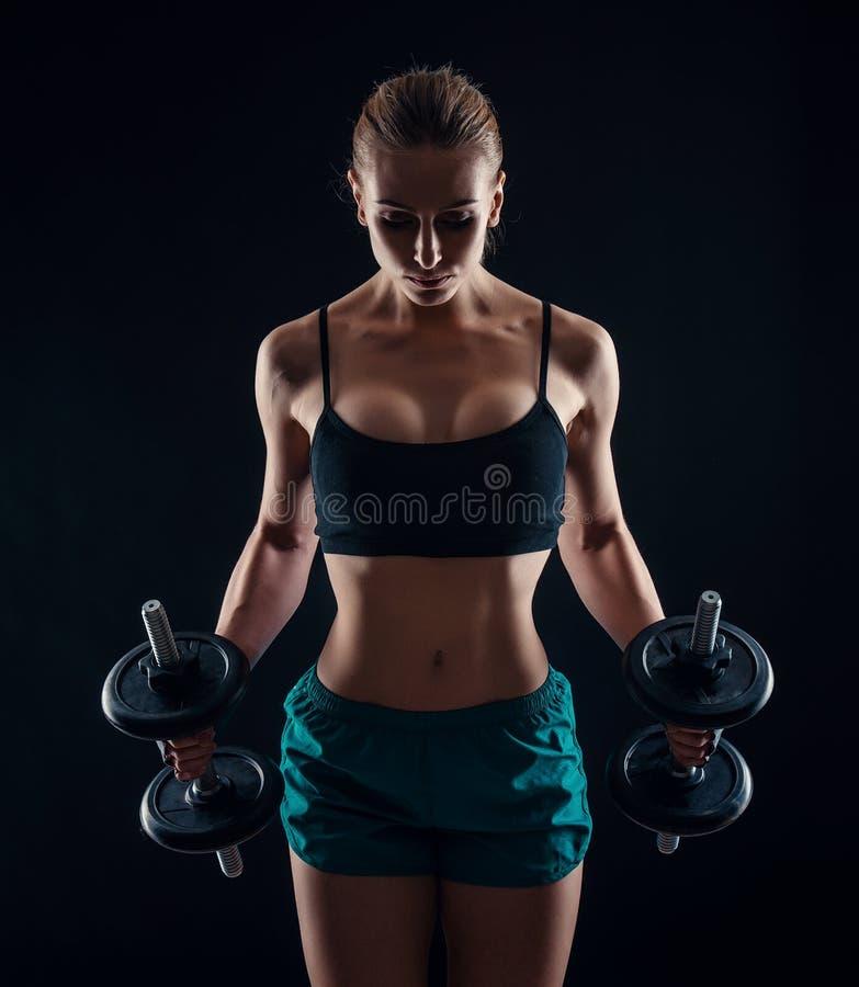 Ritratto di giovane donna di forma fisica in abiti sportivi che fanno allenamento con le teste di legno su fondo nero Ragazza atl fotografia stock libera da diritti
