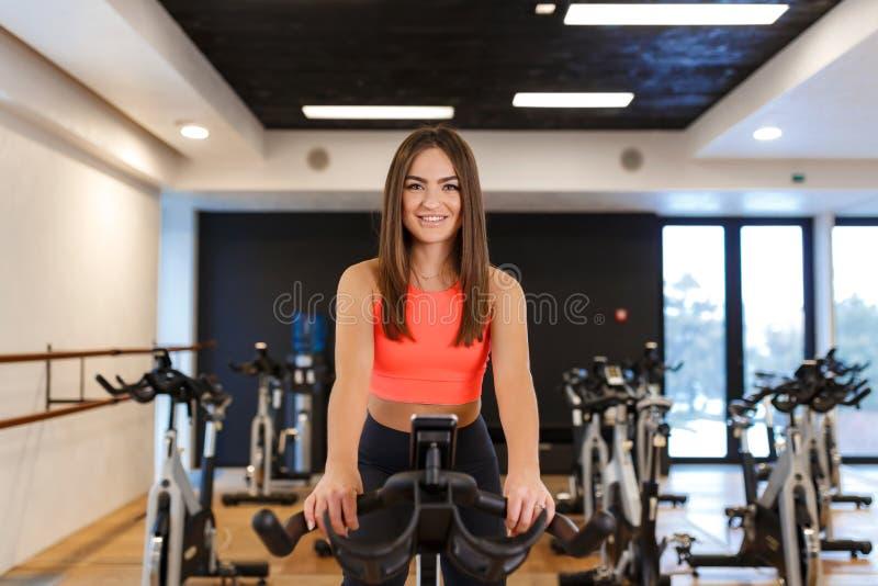 Ritratto di giovane donna esile nell'allenamento di sportwear sulla bici di esercizio in palestra Concetto di stile di vita di be fotografie stock