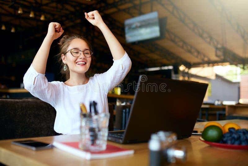 Ritratto di giovane donna felice di affari che celebra successo con le armi su davanti al computer portatile Femmina della corsa  immagini stock