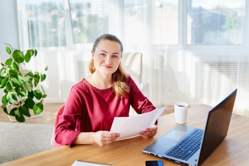 Ritratto di giovane donna felice di affari che si siede allo scrittorio di legno con il computer portatile e che lavora con i doc fotografia stock libera da diritti