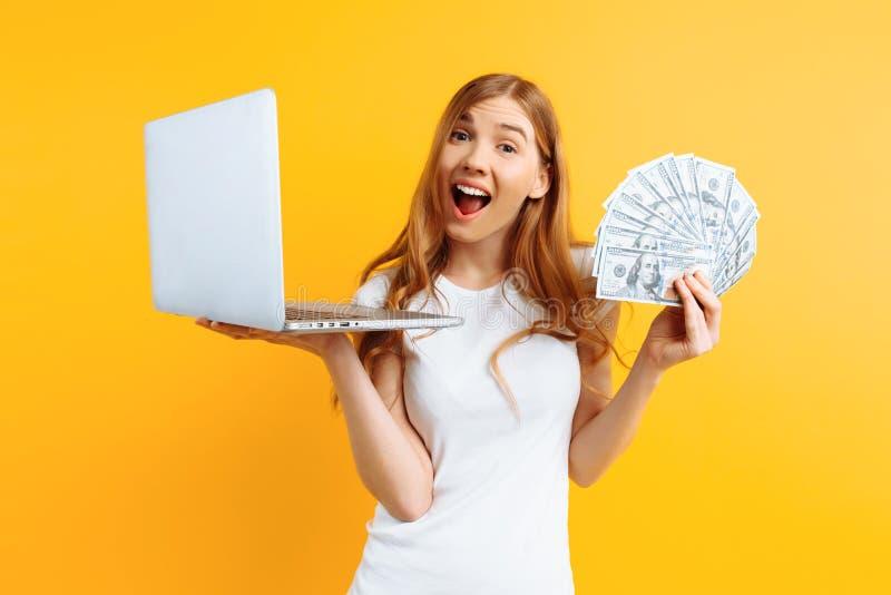 Ritratto di giovane donna felice che dura, facendo uso di un computer portatile del computer portatile e tenente soldi in mano, s fotografie stock