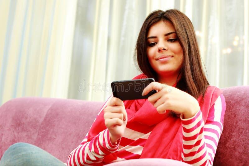 Ritratto di giovane donna felice che per mezzo dello smartphone fotografie stock