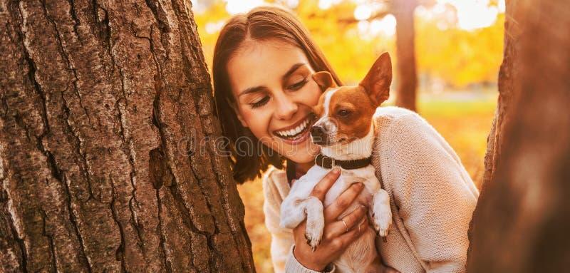 Ritratto di giovane donna felice che tiene piccolo cane sveglio immagini stock