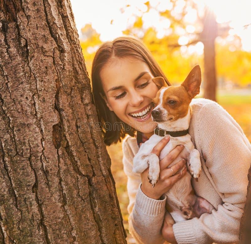 Ritratto di giovane donna felice che tiene piccolo cane sveglio immagine stock libera da diritti
