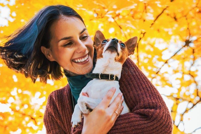 Ritratto di giovane donna felice con il piccolo cane sveglio in parco fotografie stock libere da diritti