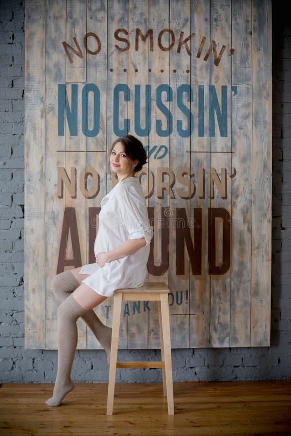 Ritratto di giovane donna incinta in camicia bianca nello studio della foto fotografia stock