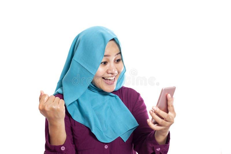 Ritratto di giovane donna musulmana asiatica ottenere buone notizie sul suo telefono, espressione sorpresa felice immagine stock