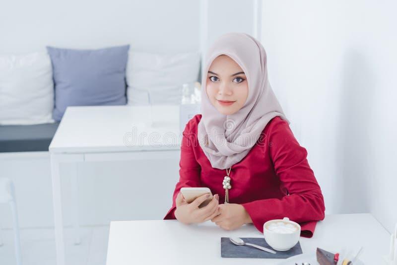 Ritratto di giovane donna musulmana felice che per mezzo del suo cellulare fotografia stock
