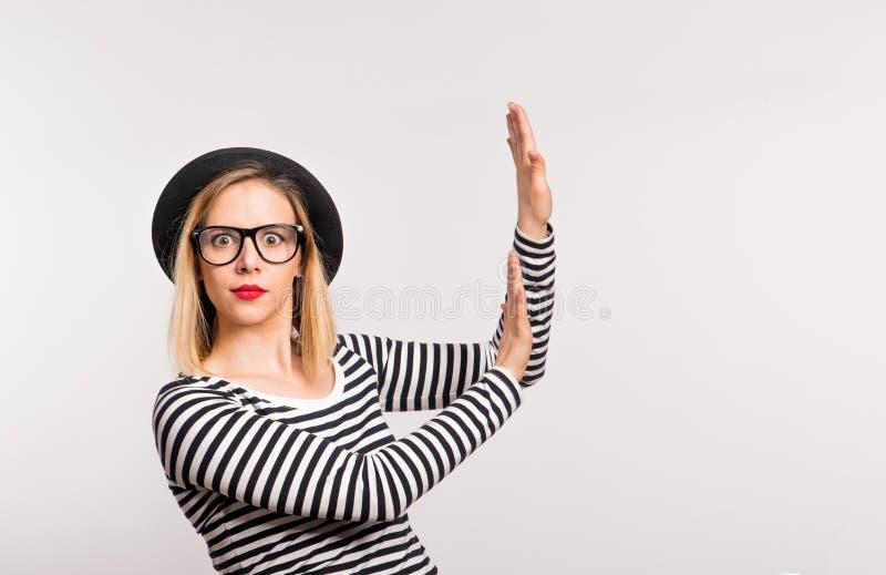 Ritratto di giovane donna preoccupata con black hat in uno studio su un fondo bianco immagine stock libera da diritti