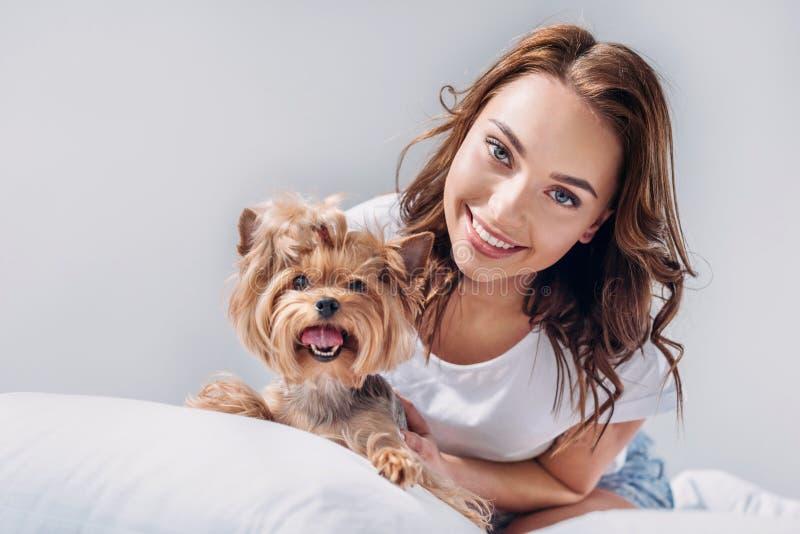 ritratto di giovane donna sorridente con l'Yorkshire terrier che riposa sul letto fotografia stock libera da diritti